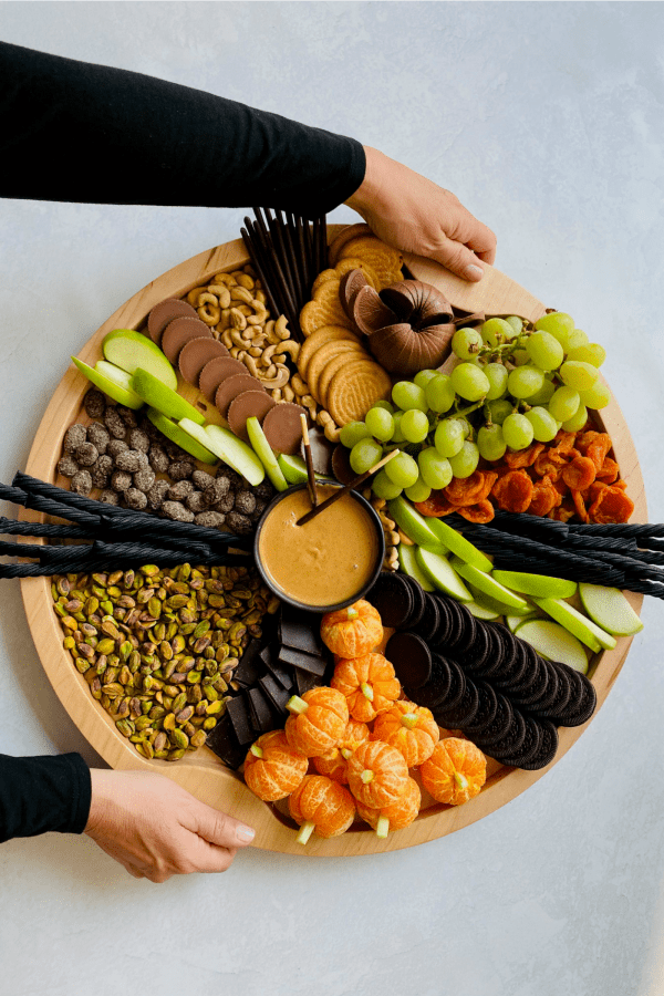 holding a round halloween snack board