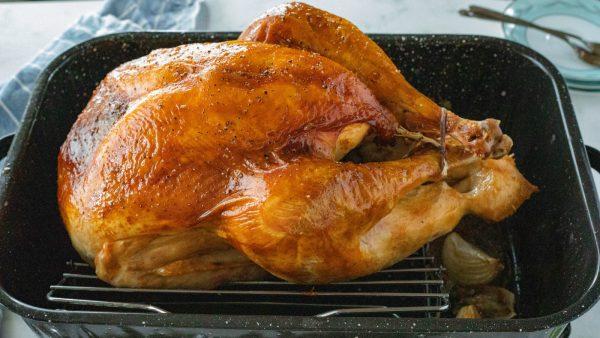 a whole bird (Apple Cider-Brined Turkey) in baking pan