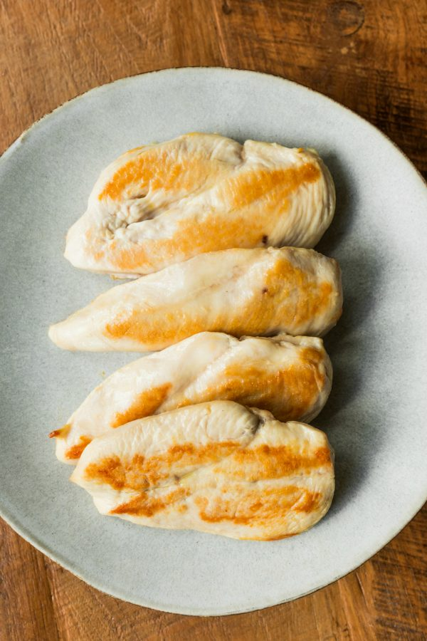 4 chicken breasts cooked and served on a plate