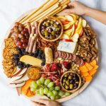 holding a round charcuterie board with winter snacks