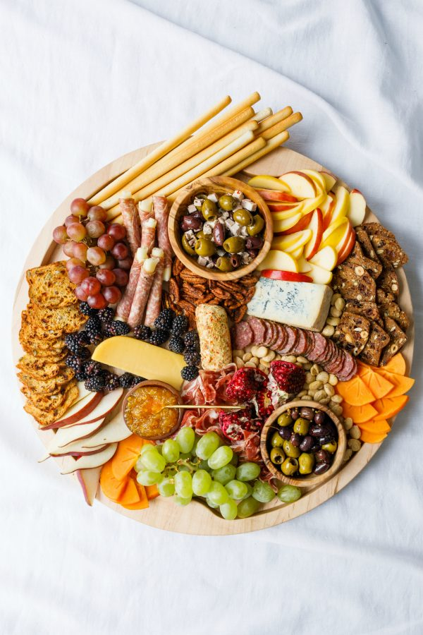 charcuterie board with crackers, apples, cheese, meats, and more