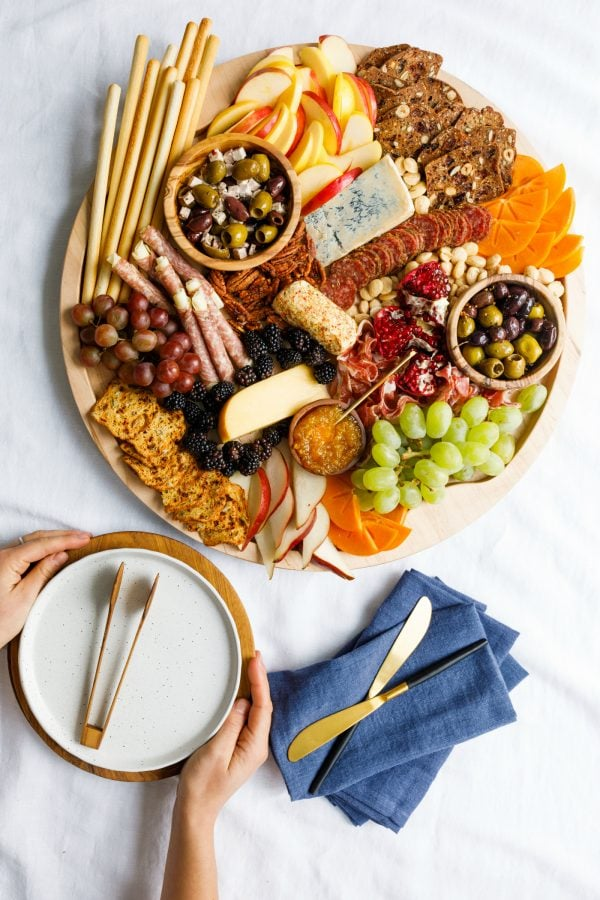 festive, winter round charcuterie board with plates and napkins