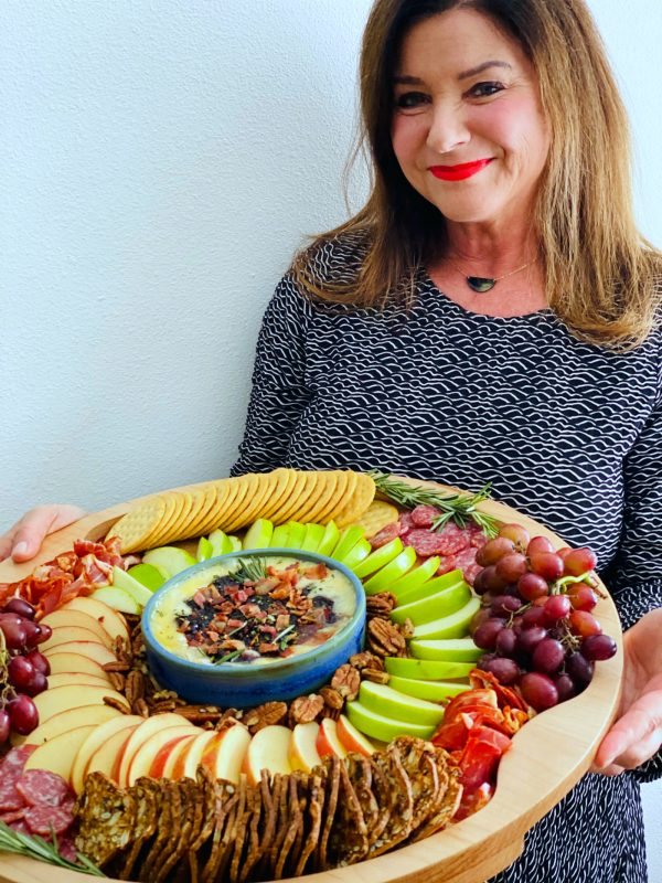 a woman holding a winter round charcuterie board