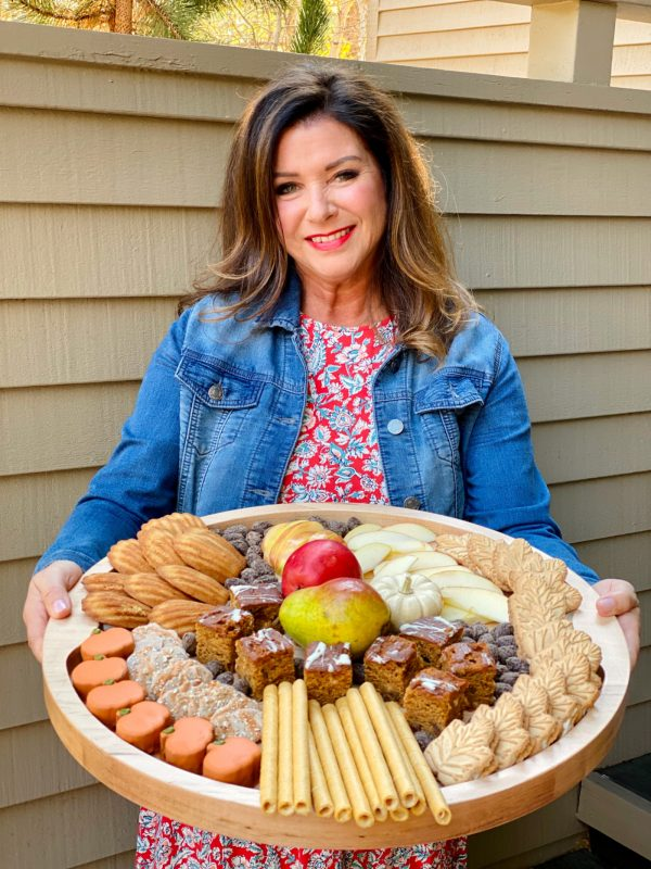 woman holding a round wood board with sweet fall snacks