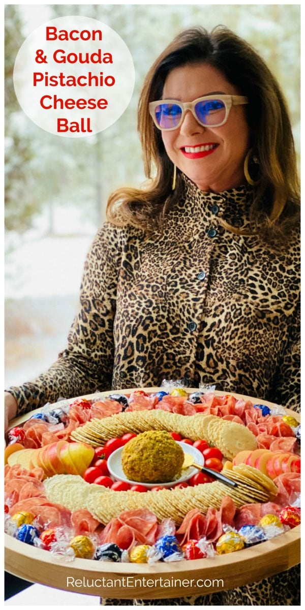 lady holding a big board with Bacon Gouda Pistachio Cheese Ball in the center