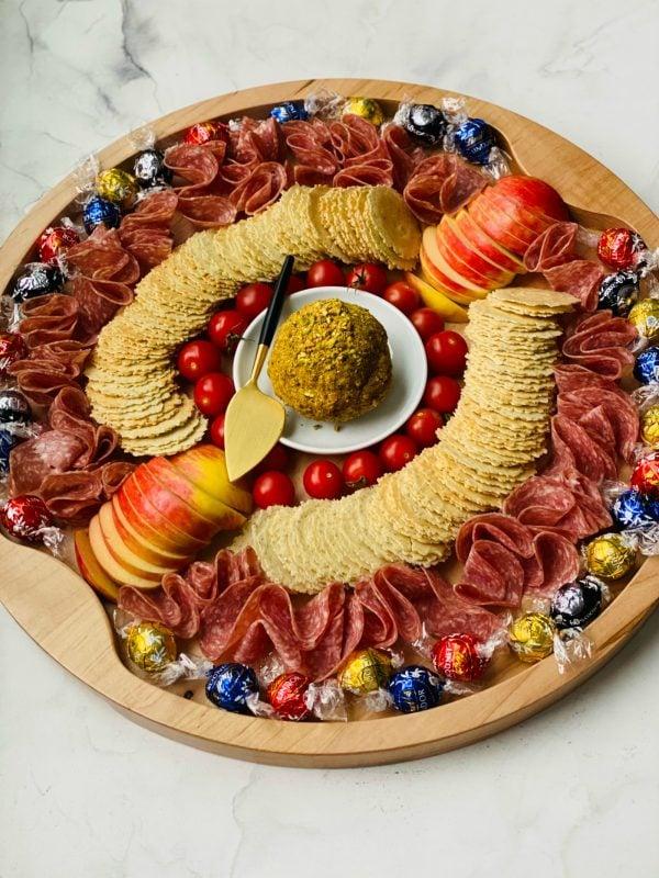 a board with Bacon Gouda Pistachio Cheese Ball in the center