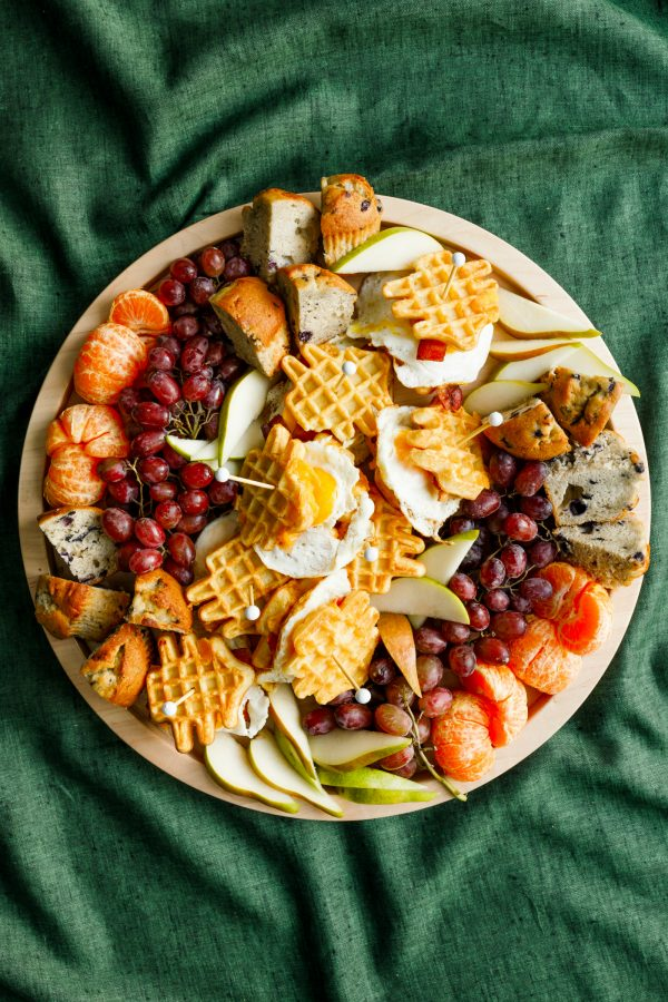 round wood tray with breakfast foods and waffle egg sandwiches