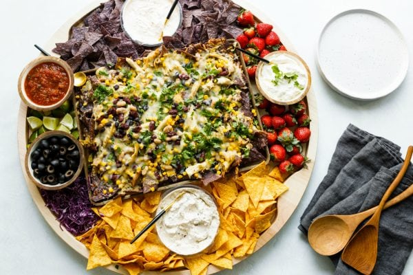 nacho board with chips, dips, and strawberries on wood board