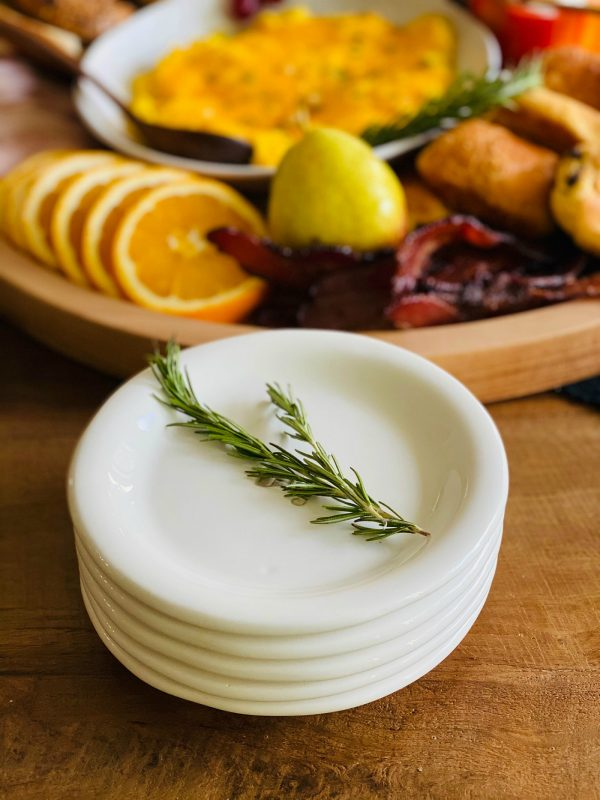 stack of white dishes (with sprig of rosemary)