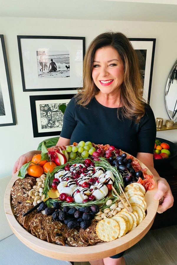 woman holding a holiday Winter Burrata Charcuterie Board