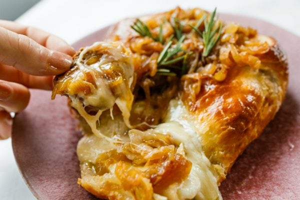 taking a cheesy bite of Onion Brie En Croute