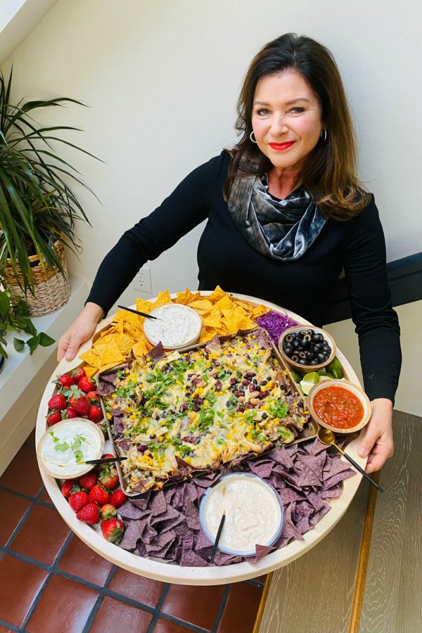 woman holding a big round board with nachos and dips