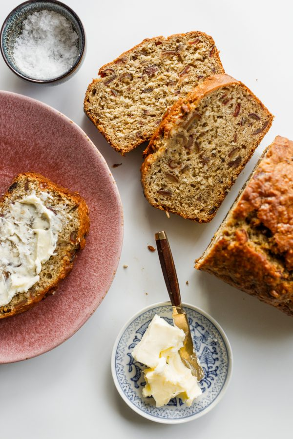 loaf of banana date bread and a slice with butter