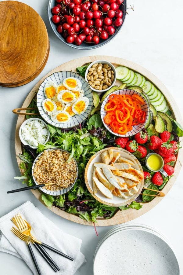 Chicken Faro Salad Board on a round board with serving dishes