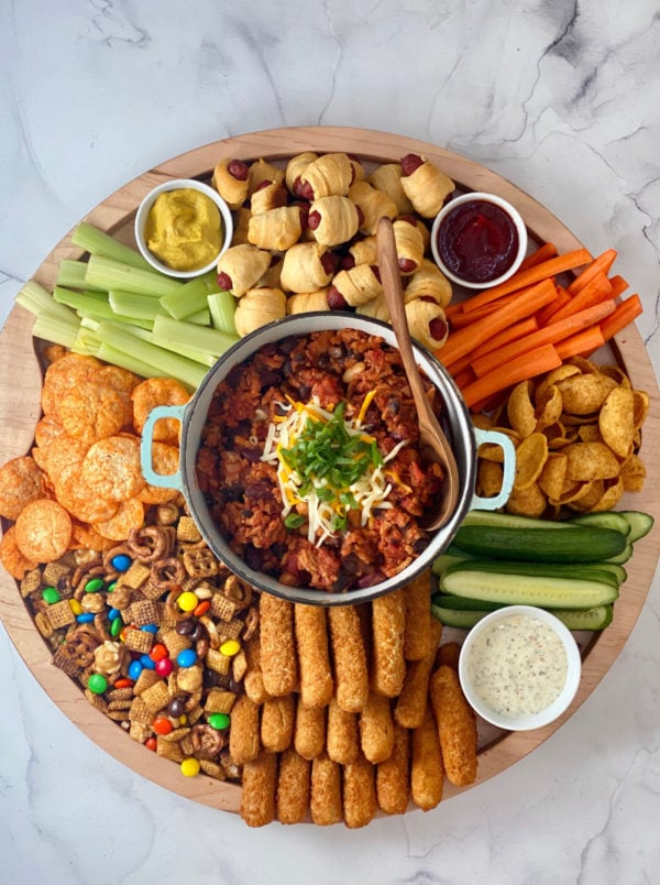 round board with chili and game day snacks
