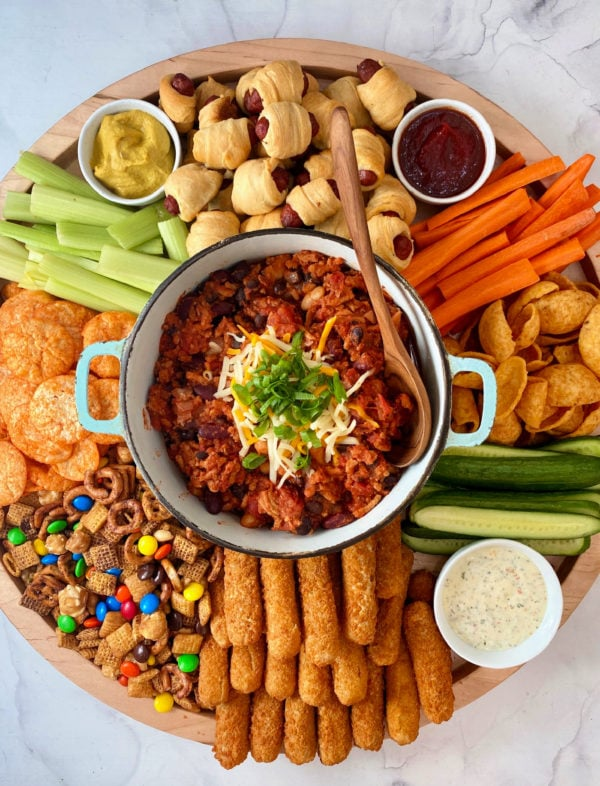 round board with pot of chili in center, surrounded by game day snacks