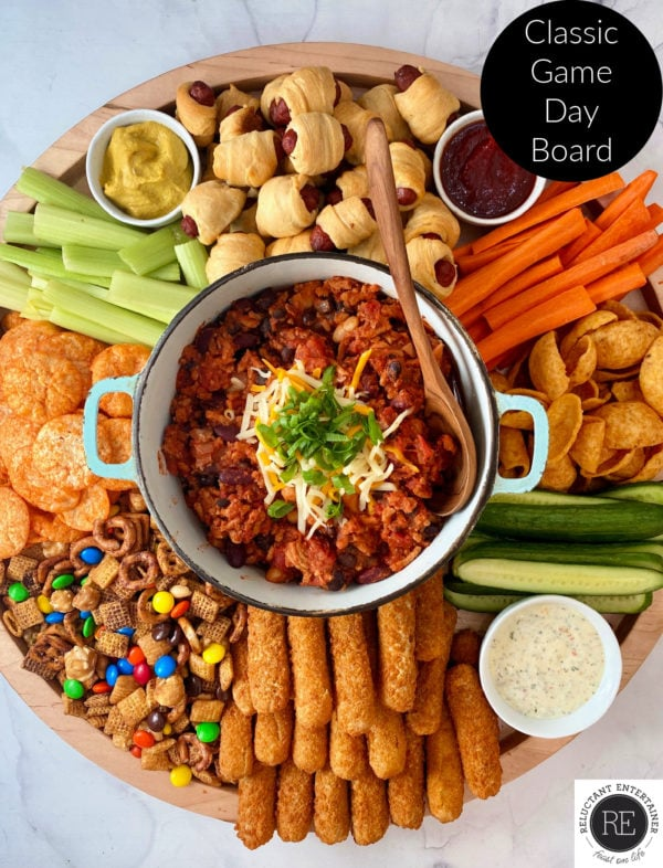 chili in the center of a game day board with cheese sticks, veggies, dips, chips