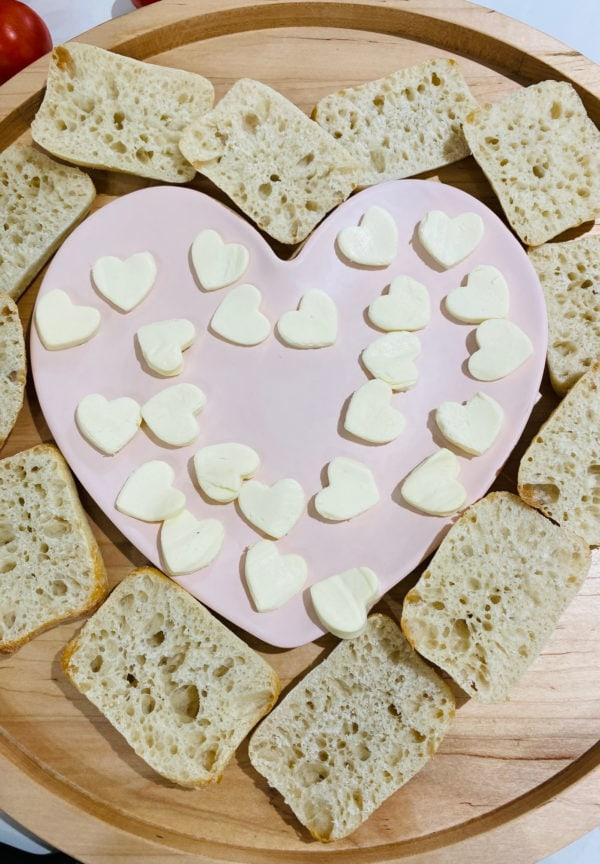 making Heart Caprese Sandwich Board with mozzarella cheese