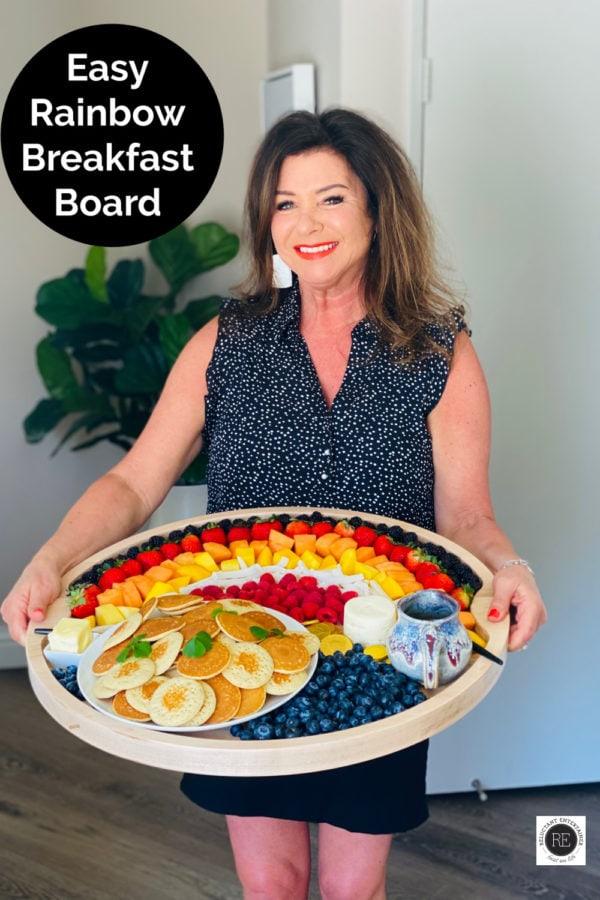 woman holding a rainbow breakfast board