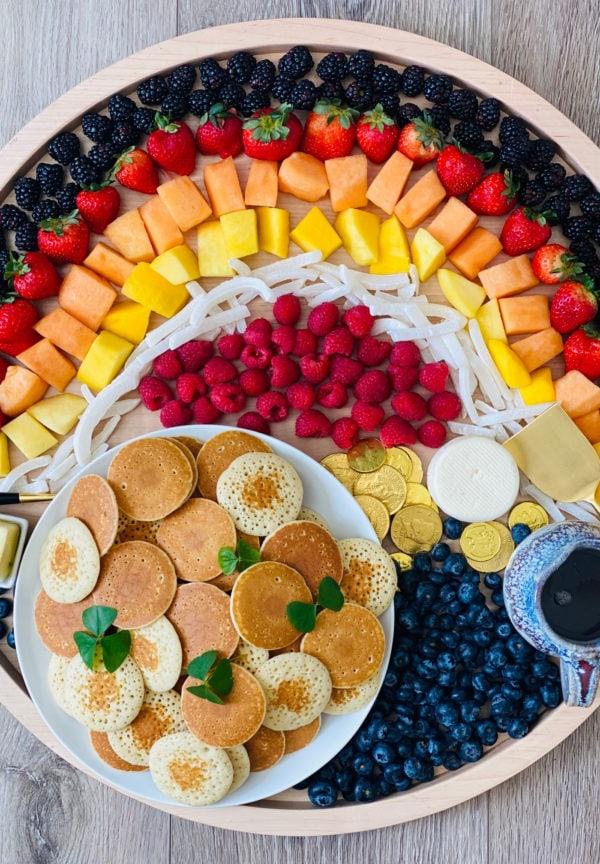 fruit shaped like a rainbow on a breakfast board