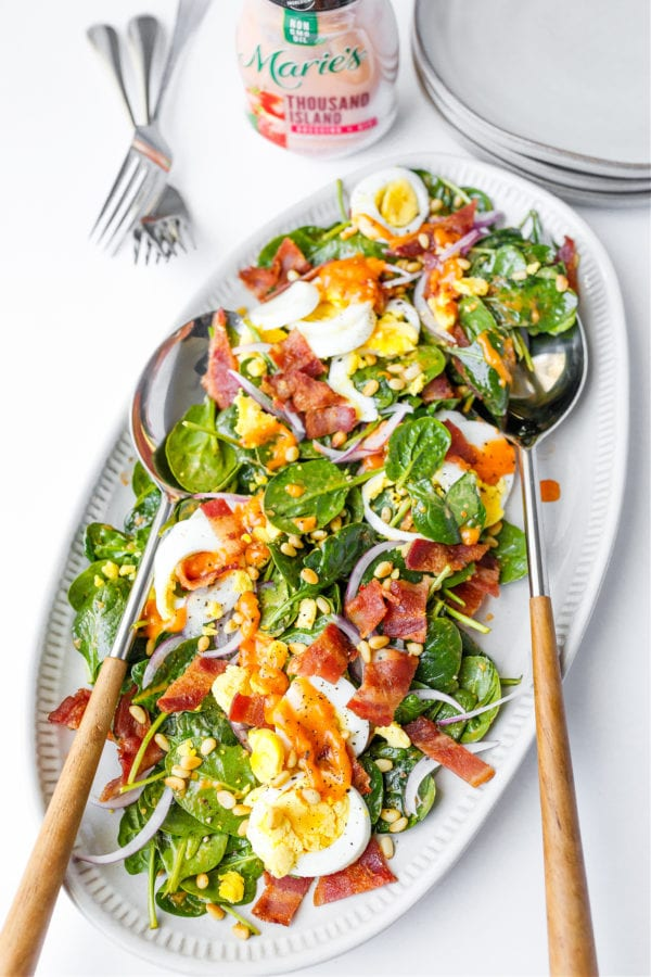 oval platter of Spinach Salad with Warm Bacon Dressing