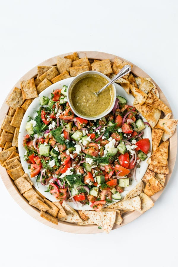 round plate of Tomato Cucumber Herb Salad with pita bread