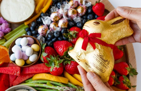 holding a gold chocolate bunny with red ribbon