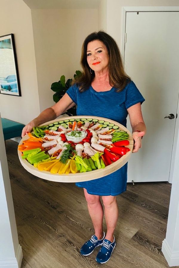 woman holding a round zero point charcuterie board