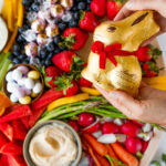 chocolate bunny with red ribbon wrapped in gold