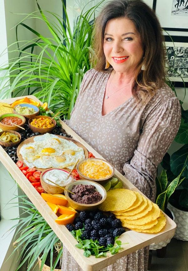 woman holding breakfast tostada board