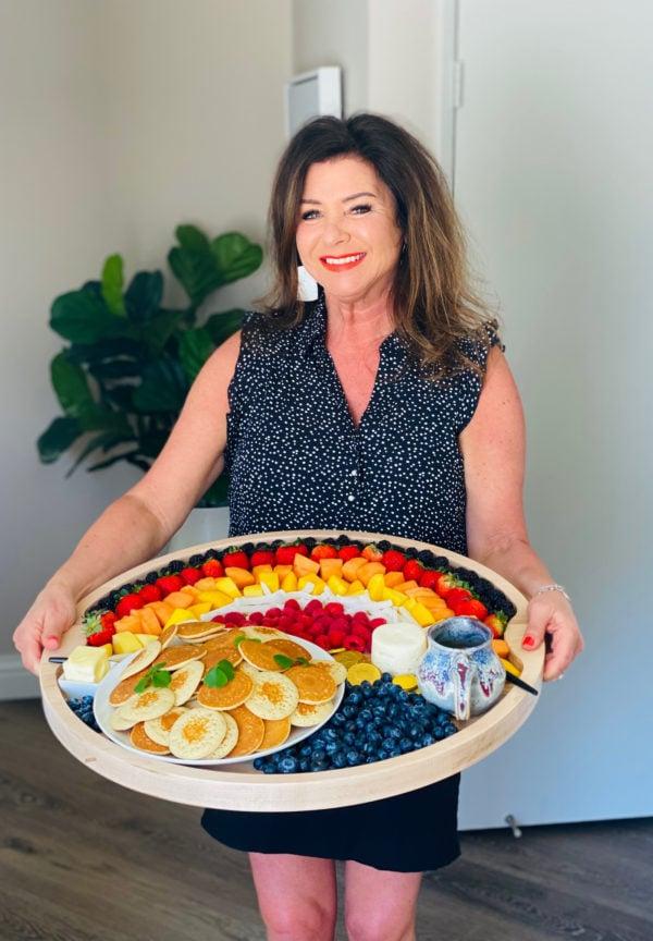 woman holding an Easy Rainbow Breakfast Board