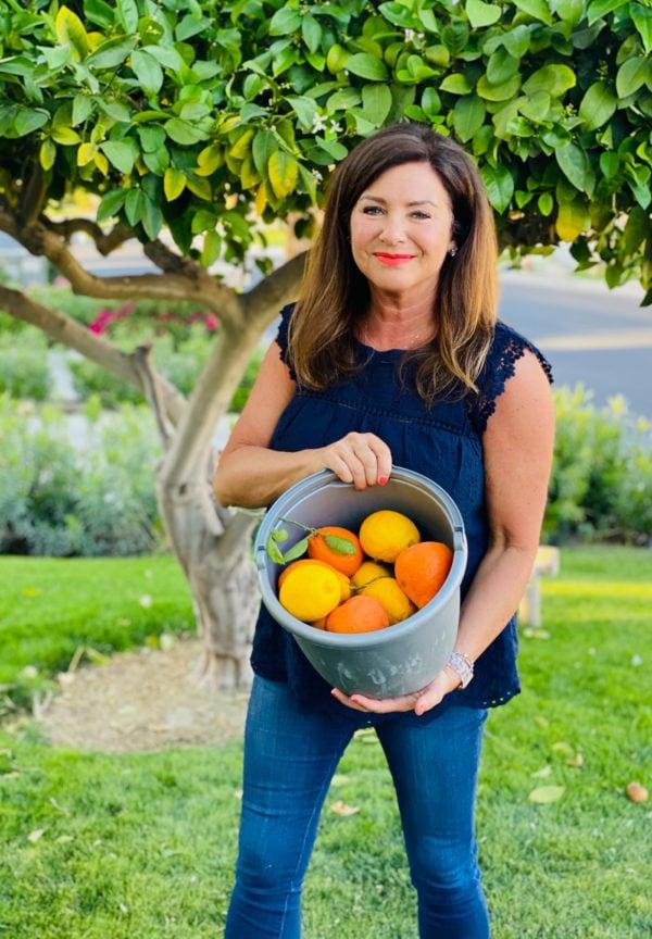woman holding bucket of oranges and Meyer lemons