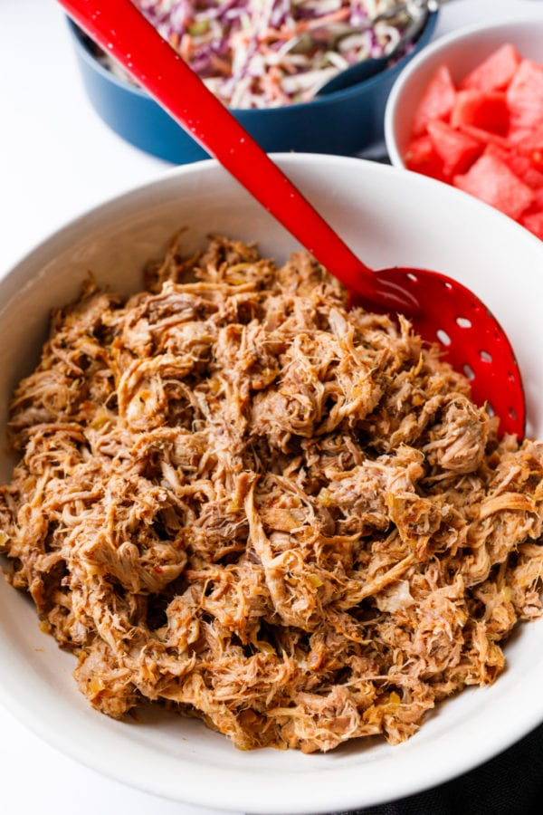 serving Slow Cooker BBQ Pulled Pork with red spoon