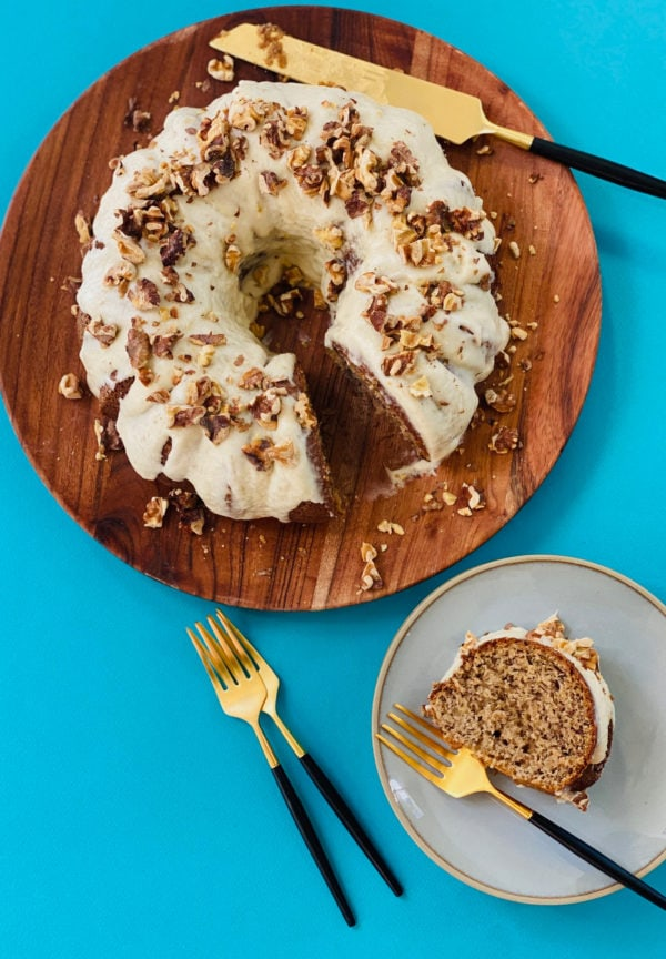 Sour Cream Banana Bundt cake on a wood plate with a slice on a plate with fork