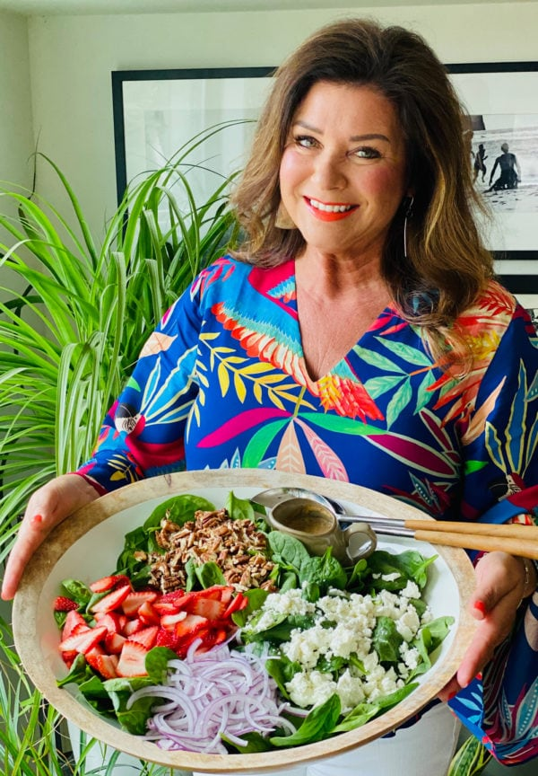 woman holding a large white bowl of My Favorite Strawberry Spinach Salad