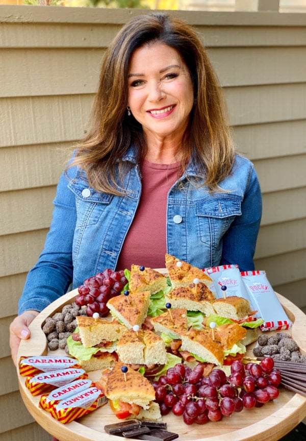 woman holding a BLT Focaccia Board with fruit and chocolate