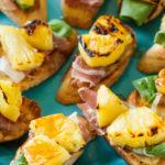 Pineapple Prosciutto Crostini on blue plates