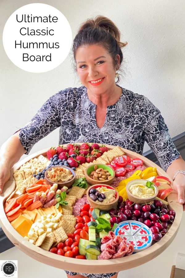 woman holding a round big board with hummus
