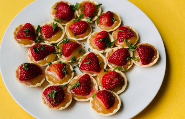 white plate of tarts with lemon and strawberries