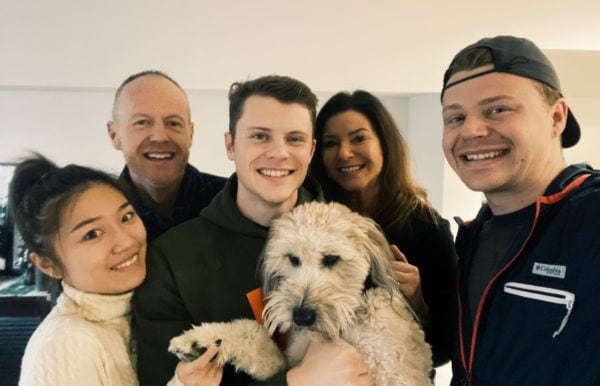 family together holding a whoodle dog