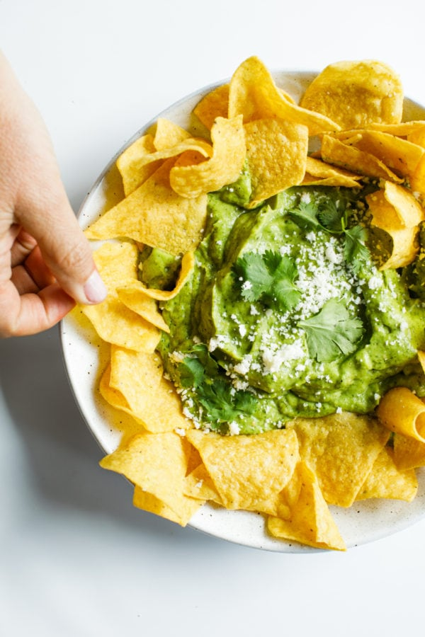 taking a bite of chip with Best Avocado Salsa Verde