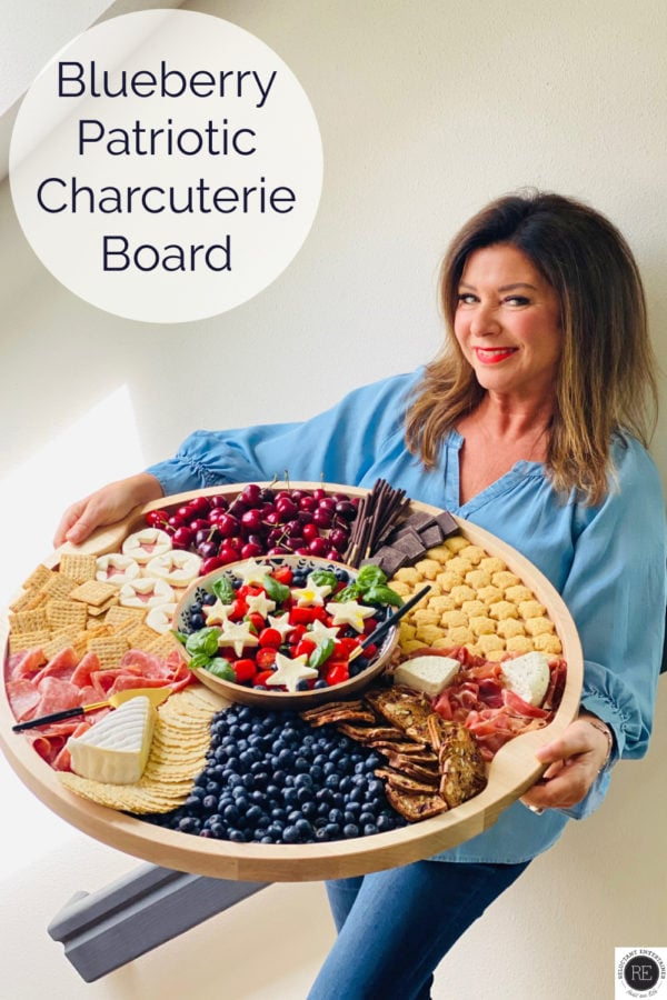 woman holding a big board with patriotic charcuterie foods