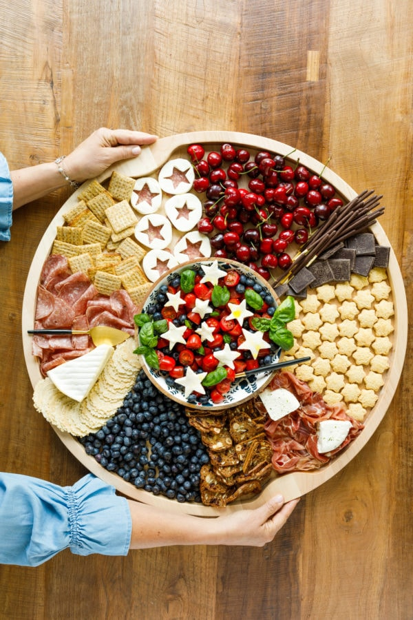 holding a round blueberry patriotic charcuterie board