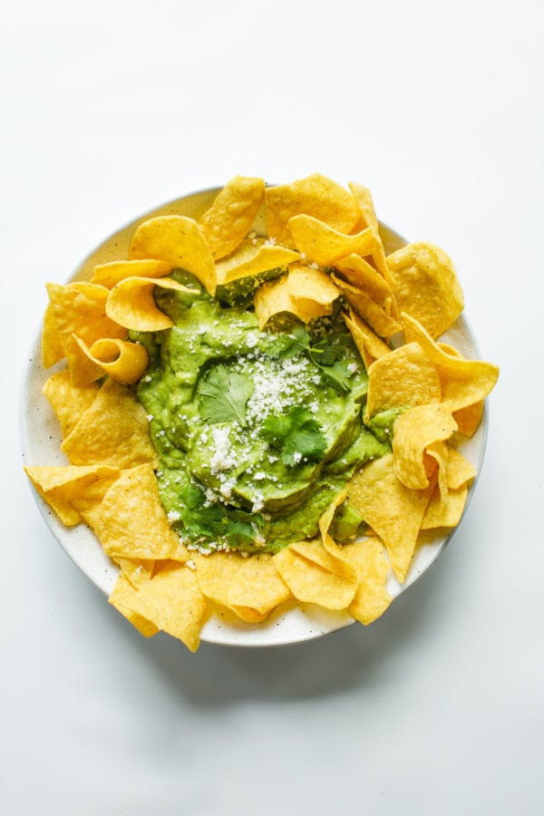 round platter of chips with Best Avocado Salsa Verde