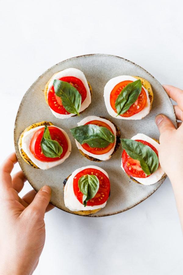 making a plate of Grilled Polenta Caprese Appetizer