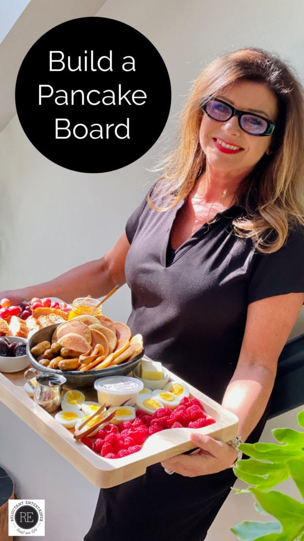 woman holding a big board with pancake breakfast