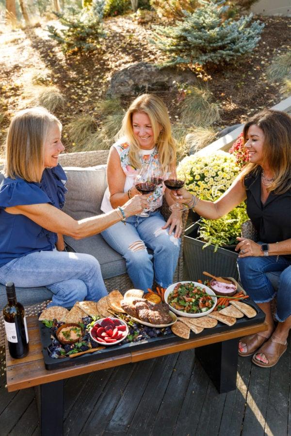 3 women with wine and pita burger board