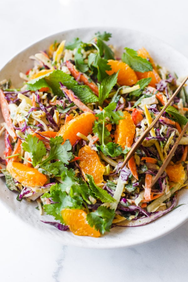 bowl of Crunchy Cashew Cabbage Salad with tongs