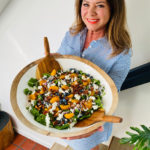 woman holding big white bowl spinach salad