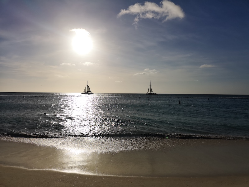 Sailboats in late afternoon moored off a beach in Aruba